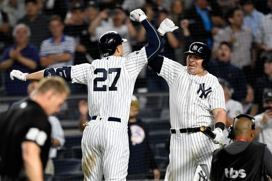 New York Yankees' Giancarlo Stanton (27) and Luke Voit, right, celebrate Stanton's solo home run in the eighth inning against the Oakland Athletics in the American League Wildcard game on Wednesday, Oct. 3, 2018, in New York.