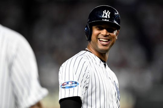 New York Yankees' Aaron Hicks smiles at third base after Aaron Judge (not pictured) scores in the sixth inning off of his double in the American League Wildcard game on Wednesday, Oct. 3, 2018, in New York.