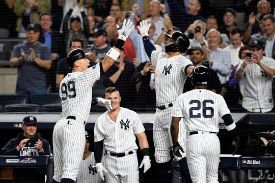 New York YankeesÕ Aaron Judge (99) and Giancarlo Stanton, right, high-five at home plate after Judge's two-run home run in the first inning against the Oakland Athletics in the American League Wildcard game on Wednesday, Oct. 3, 2018, in New York.