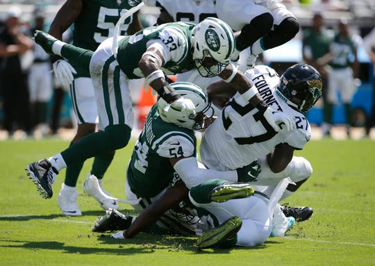 Jacksonville Jaguars running back Leonard Fournette (27) is stopped by the New York Jets defense including Jamal Adams (33) and Avery Williamson (54) during the first half of an NFL football game, Sunday, Sept. 30, 2018, in Jacksonville, Fla. (AP Photo/Stephen B. Morton)