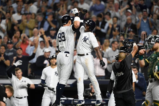 New York Yankees' Aaron Judge, left, and Andrew McCutchen, right, celebrate Judge's two-run home run at home plate in the first inning against the Oakland Athletics in the American League Wildcard game on Wednesday, Oct. 3, 2018, in New York.