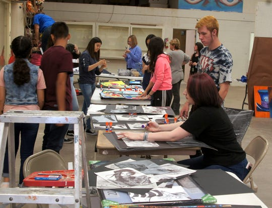 Deming High students were busy Wednesday morning preparing the art exhibit at the fairgrounds.