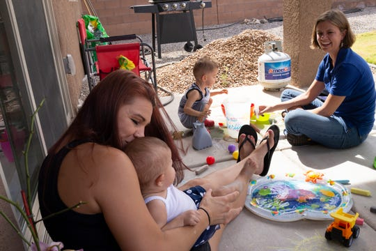 CHI St. Joseph's Children home visitor Amanda Lind, 30-month-old Lucas, Lucas' mother, Christie Ross, and sister, Chloe, play on their porch in Albuquerque during a home visit in July 2018.