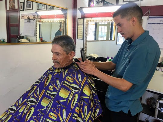 Gustavo Ceballos, co-owner of Good Life Barber Shop, 3213 S. Main St., cuts a man's hair Wednesday afternoon.