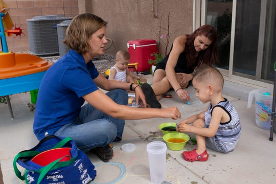 CHI St. Joseph's Children home visitor Amanda Lind helps 30-month-old Lucas pull colored water into a dropper as a fine-motor-skills activity during a home visit in Albuquerque in July 2018, while Lucas' mother, Christie Ross, and sister, Chloe, play nearby.