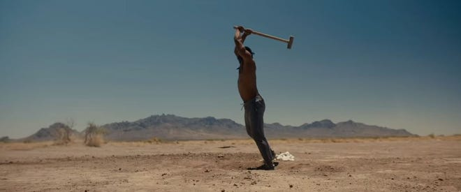 """In this screenshot from the movie """"Creed II,"""" Michael B. Jordan wields a sledgehammer. Deming's Florida Mountains appear in the background."""