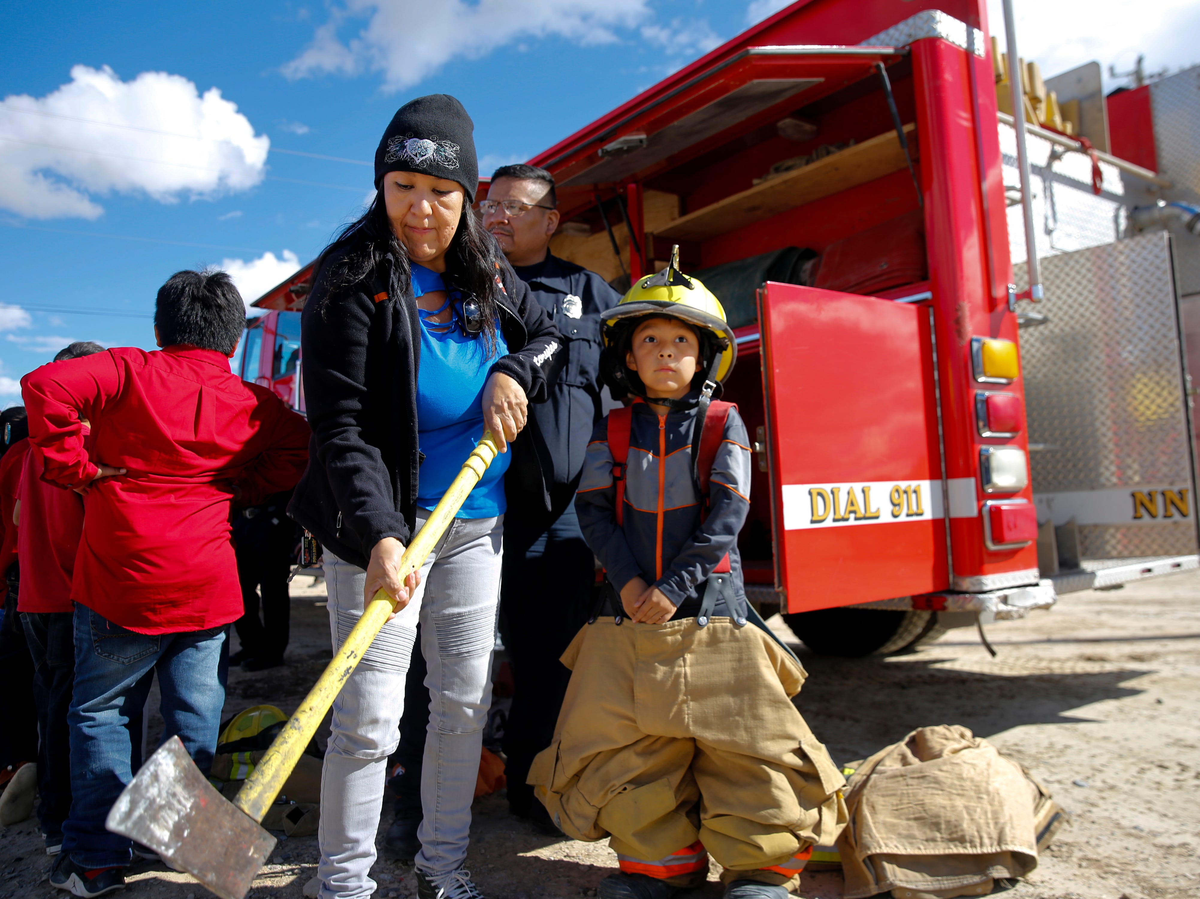 From left, Brenda Tabaha examines an ax used by members of the Navajo Nation Fire Department as her son Isaiah Tabaha, 7,  tries on firefighting gear, Thursday, Oct. 4, 2018 during the Northern Navajo Nation Fair in Shiprock.