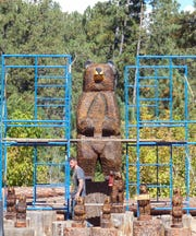 The huge bear dwarfs his smaller kin for sale at Grizzly's in Ruidoso. Carved bears are a popular item for tourists and homeowners, because of the forested village's reputation as a great place to view wildlife. Assistant Ryan Nugent provides a comparison of size.