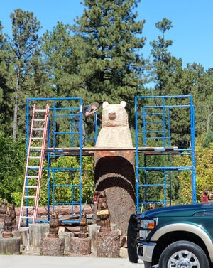 Assistant Ryan Nugent checks out a detail on a gigantic bear created by a chainsaw-wielding Grizzly Adams at his business on Sudderth Drive in Ruidoso.