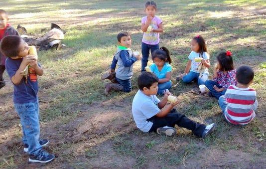 Mescalero students eat corn