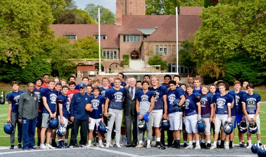 Cranbrook graduate and 1958 Heisman Trophy winner Pete Dawkins (center) proudly stands with the current football team at the Oval.