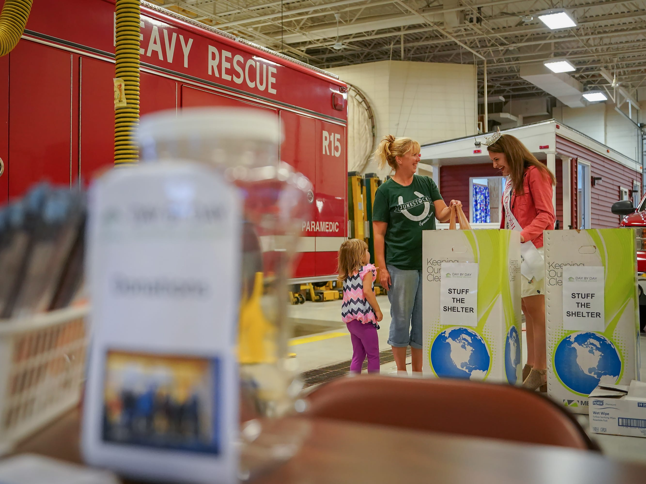 "Lisa Levenhagen and daughter Layla drop off a donation to Miss Oshkosh Kate Lidtke. The Oshkosh Day by Day Warming shelter teamed up with the Oshkosh Fire Department for ""Stuff the Shelter"" on Wednesday evening, October 3, 2018. Donations were accepted and fire station tours were given."