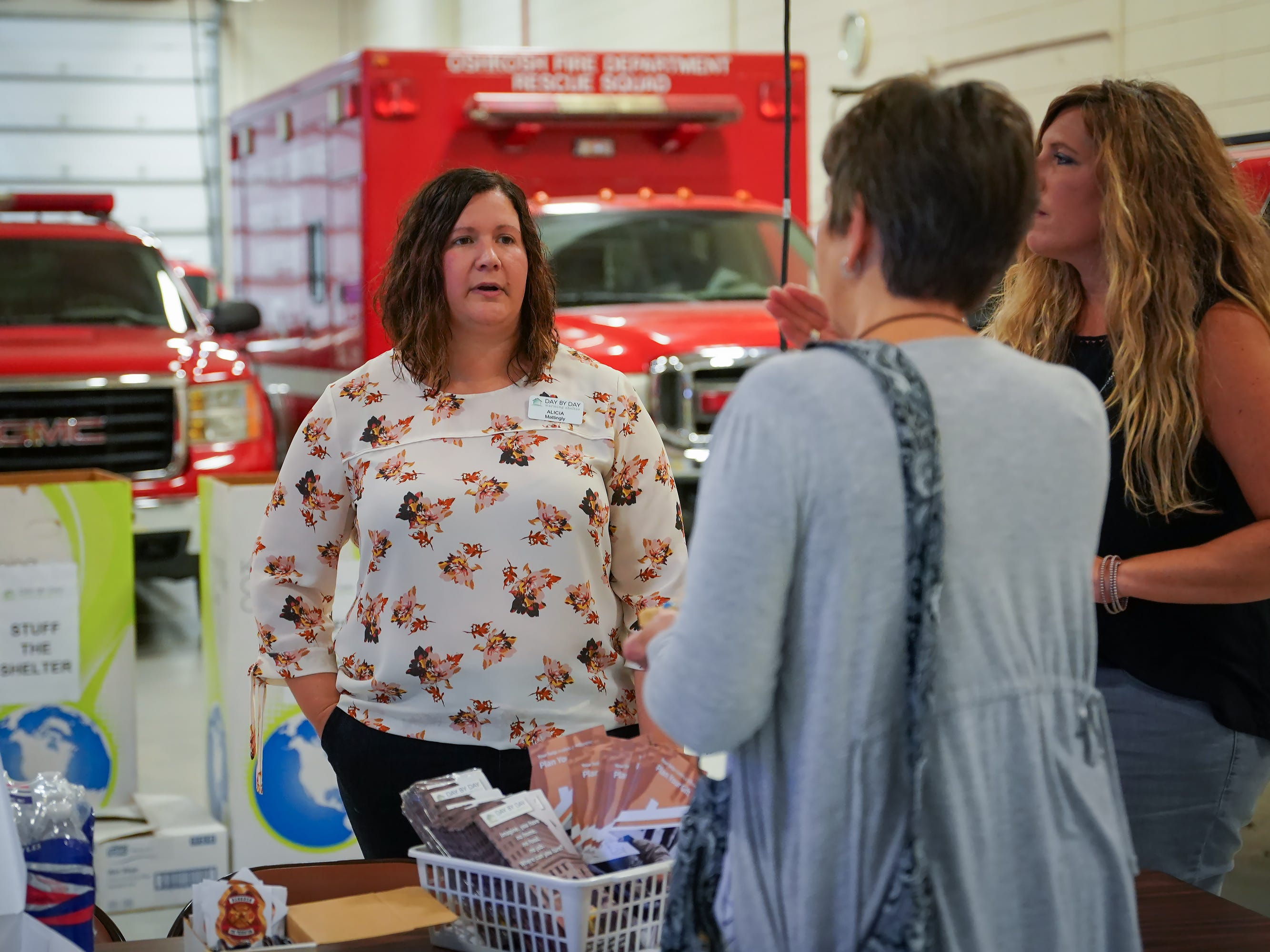 "Susan van Houwelingen talks with assistant shelter director Alicia Mattingly  and board member Carissa Pahlow. The Oshkosh Day by Day Warming shelter teamed up with the Oshkosh Fire Department for ""Stuff the Shelter"" on Wednesday evening, October 3, 2018. Donations were accepted and fire station tours were given."