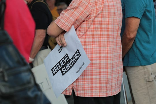 A man holds a sign in front of Palm Springs City Hall in protest of Supreme Court nominee Brett Kavanaugh on Wednesday, Oct. 3, 2018.