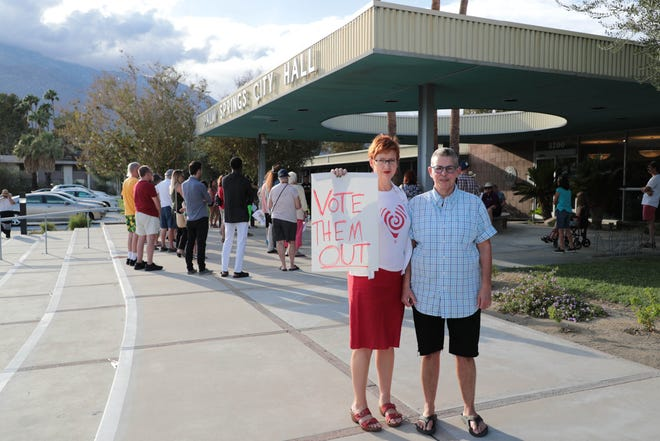A couple poses with their sign in front of Palm Springs City Hall where residents gathered in protest of Supreme Court nominee Brett Kavanaugh on Wednesday, Oct. 3, 2018.
