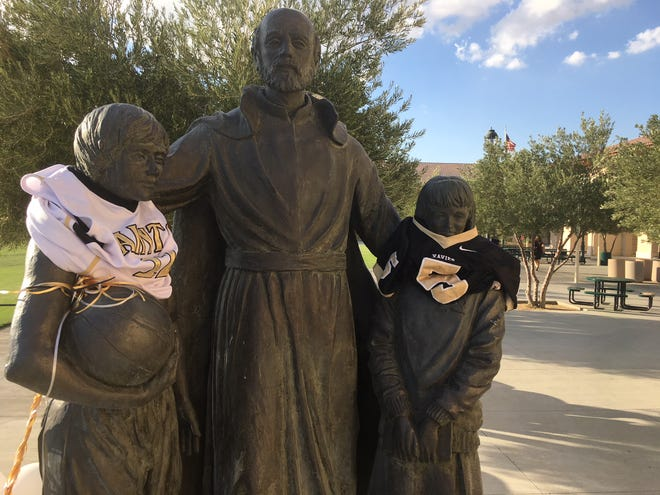 A statue on the campus of Xavier Prep High School includes the jerseys of two student athletes injured in an auto accident.