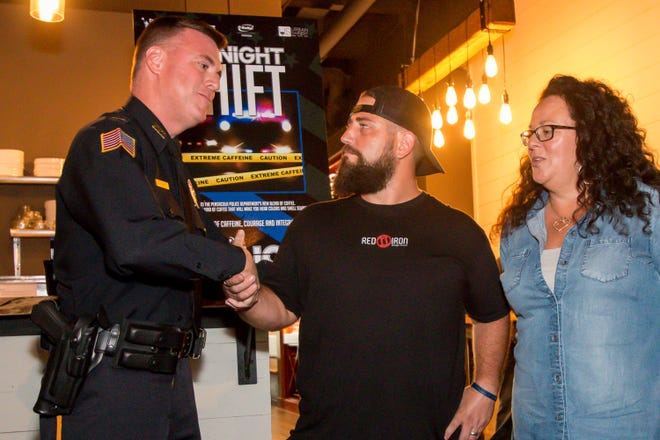 "Pensacola Police Department Capt. Steve Davis shakes hands Wednesday with Doug Jolly, owner of Red Iron Design House, as Lisa Long looks on at event to launch PPD's new brand of coffee called ""Midnight Shift"" at Urban Swinery in downtown Pensacola."