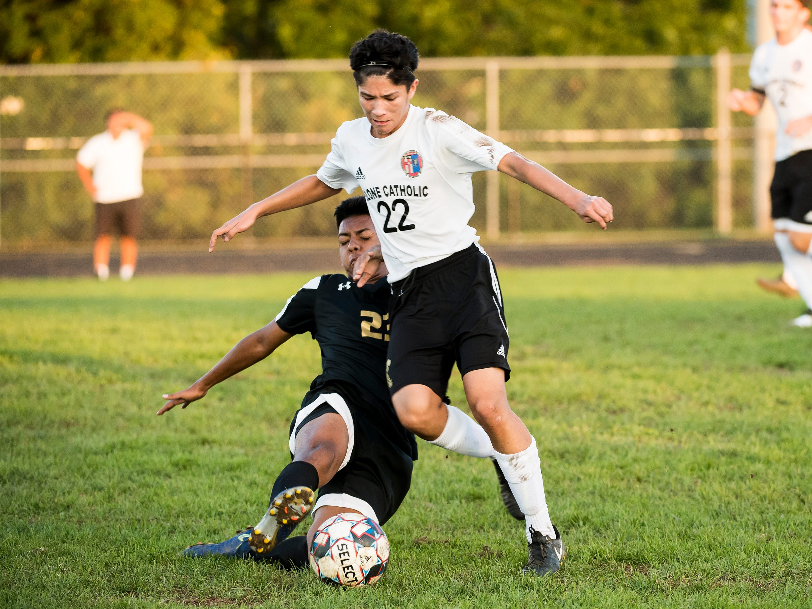 Biglerville's Carlos Castillo slides to hit the ball away from Delone Catholic's Patrick O'Donnell (22) on Wednesday, October 3, 2018. The Canners won 3-0.