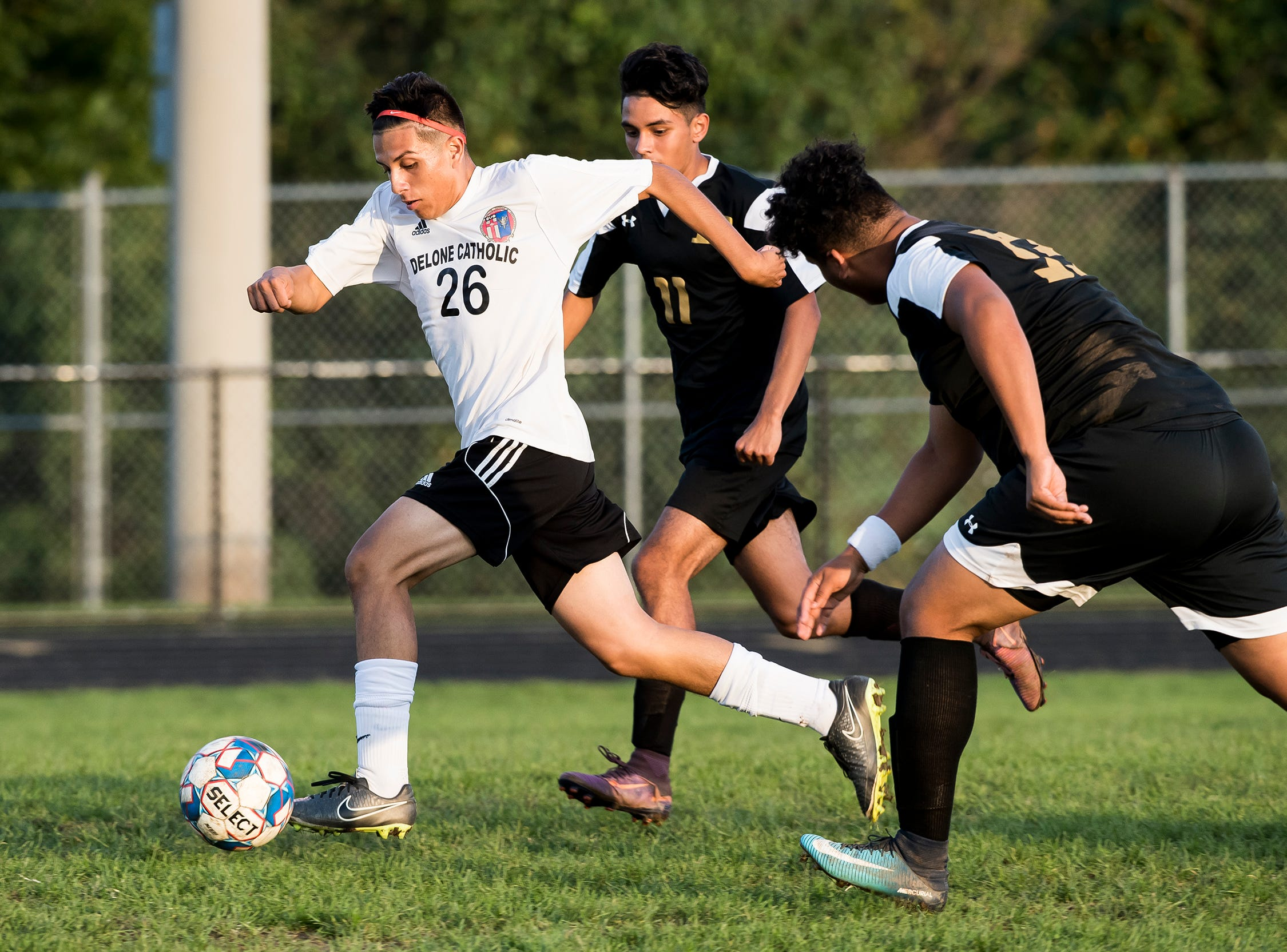 Delone Catholic's Alex Zepeda (26) breaks away from two Biglerville defenders during a game on Wednesday, October 3, 2018. The Squires fell 3-0.