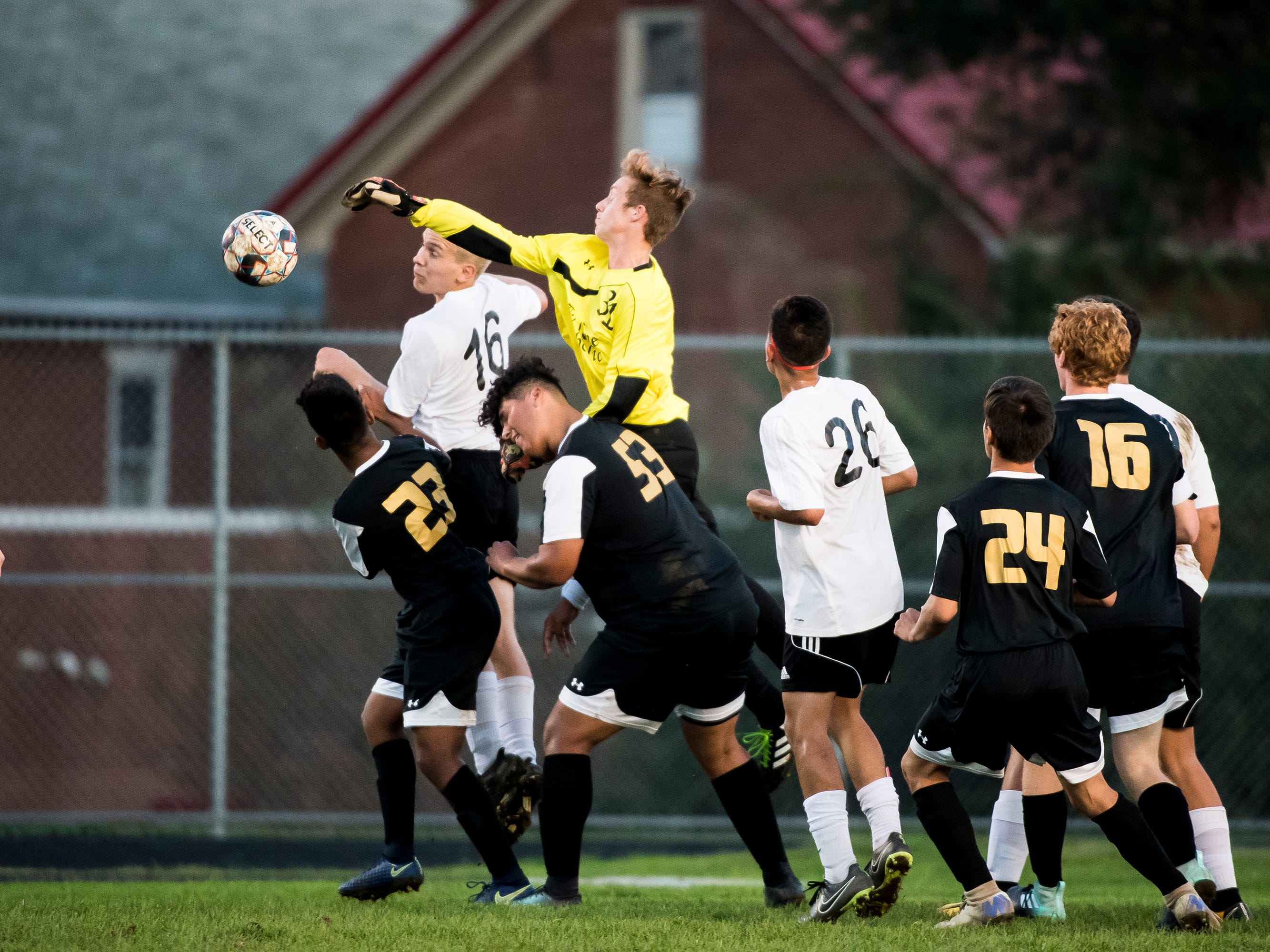 Delone Catholic goalkeeper Jacob Boccabella (yellow) comes out of the net to knock away a shot from Biglerville on Wednesday, October 3, 2018. The Canners won 3-0.