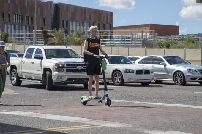 A man rides a scooter in Tempe on Oct. 4, 2018. Tempe is debating whether to begin regulating the shareable bicycles and electric scooters that are now prolific in downtown Tempe and at Arizona State University.
