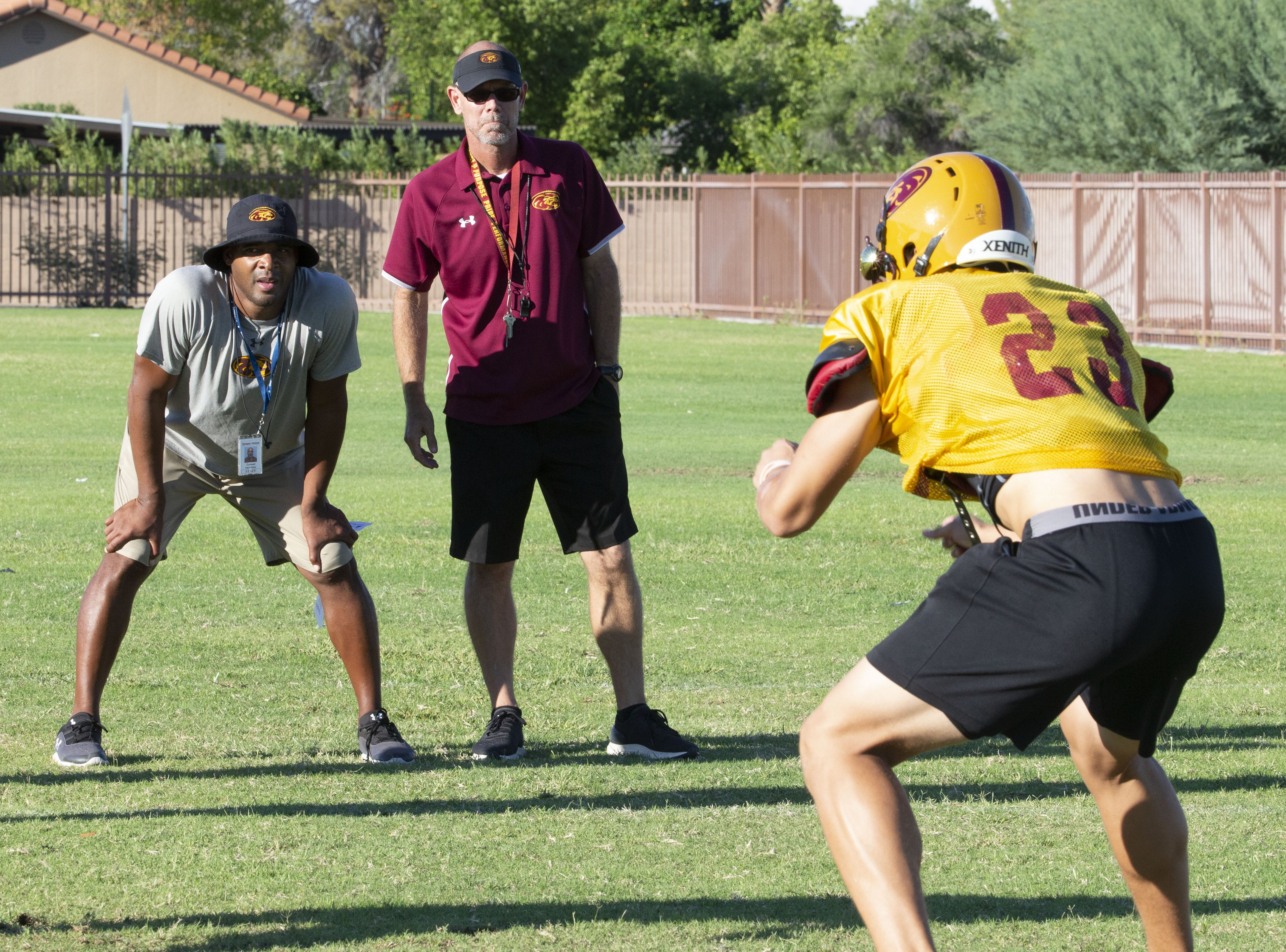 Mountain Pointe's defensive coordinator Conrad Hamilton, left,  and head coach Rich Wellbroch watches a drill during practice in Phoenix on October 3, 2018.