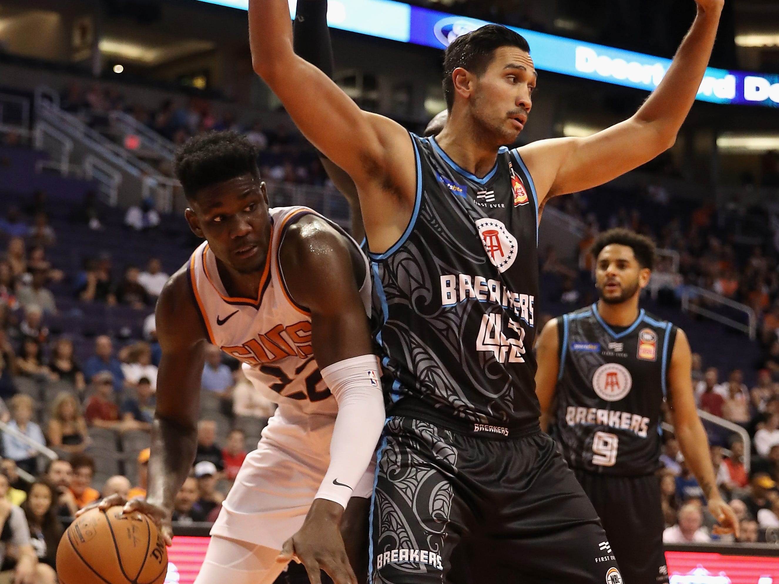 PHOENIX, AZ - OCTOBER 03:  Deandre Ayton #22 of the Phoenix Suns handles the ball against Tai Wesley #42 of the New Zealand Breakers during the first half of the NBA game at Talking Stick Resort Arena on October 3, 2018 in Phoenix, Arizona.  NOTE TO USER: User expressly acknowledges and agrees that, by downloading and or using this photograph, User is consenting to the terms and conditions of the Getty Images License Agreement.  (Photo by Christian Petersen/Getty Images)