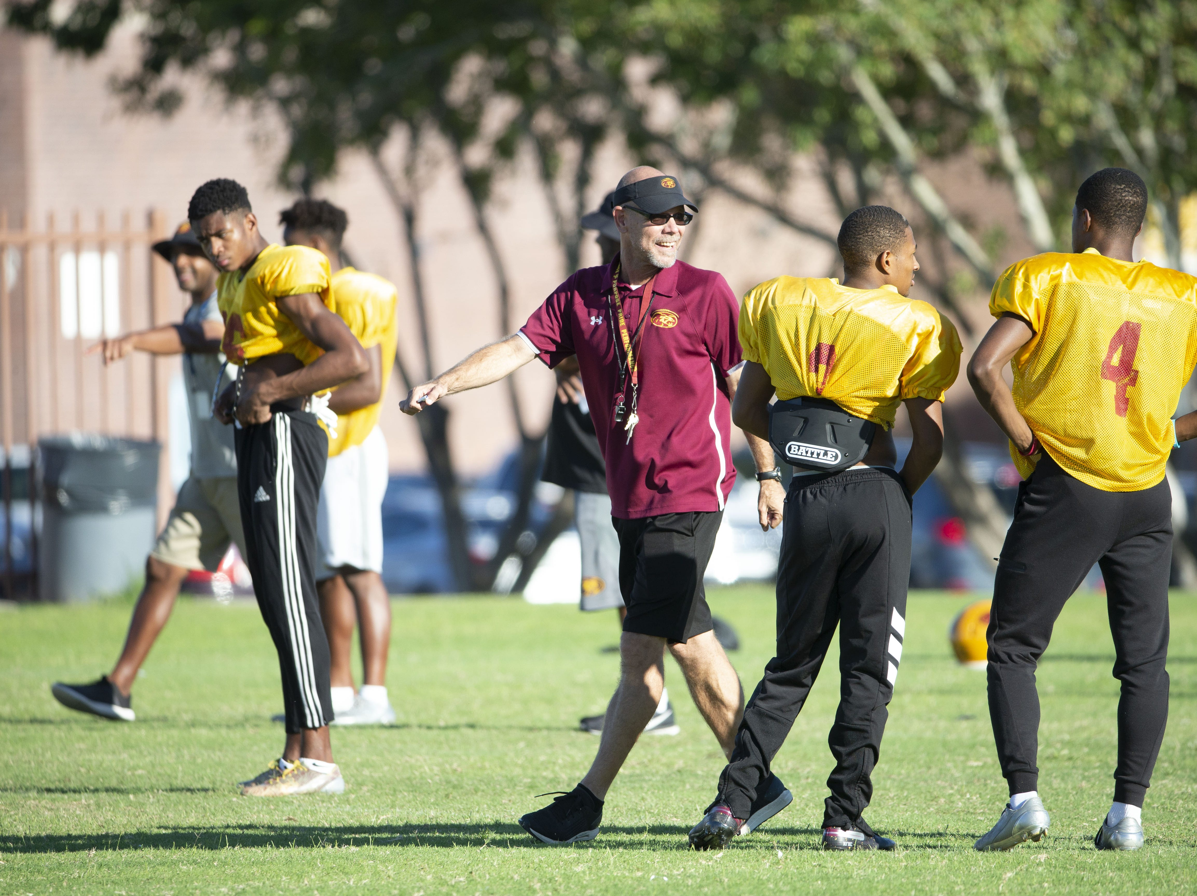 Mountain Pointe's head football coach Rich Wellbroch jokes with his players during practice in Phoenix on October 3, 2018.