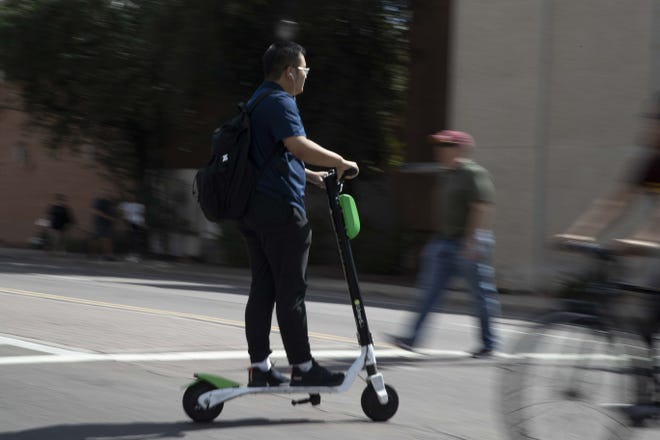 A man rides a scooter Oct. 4, 2018, in Tempe. Tempe is debating whether to begin regulating the shareable bicycles and electric scooters that are now prolific in downtown Tempe and at Arizona State University.