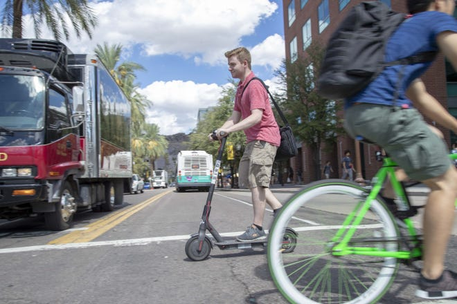 Nick Walker rides a scooter Oct. 4, 2018, in Tempe. Tempe is debating whether to begin regulating the shareable bicycles and electric scooters that are now prolific in downtown Tempe and at Arizona State University.