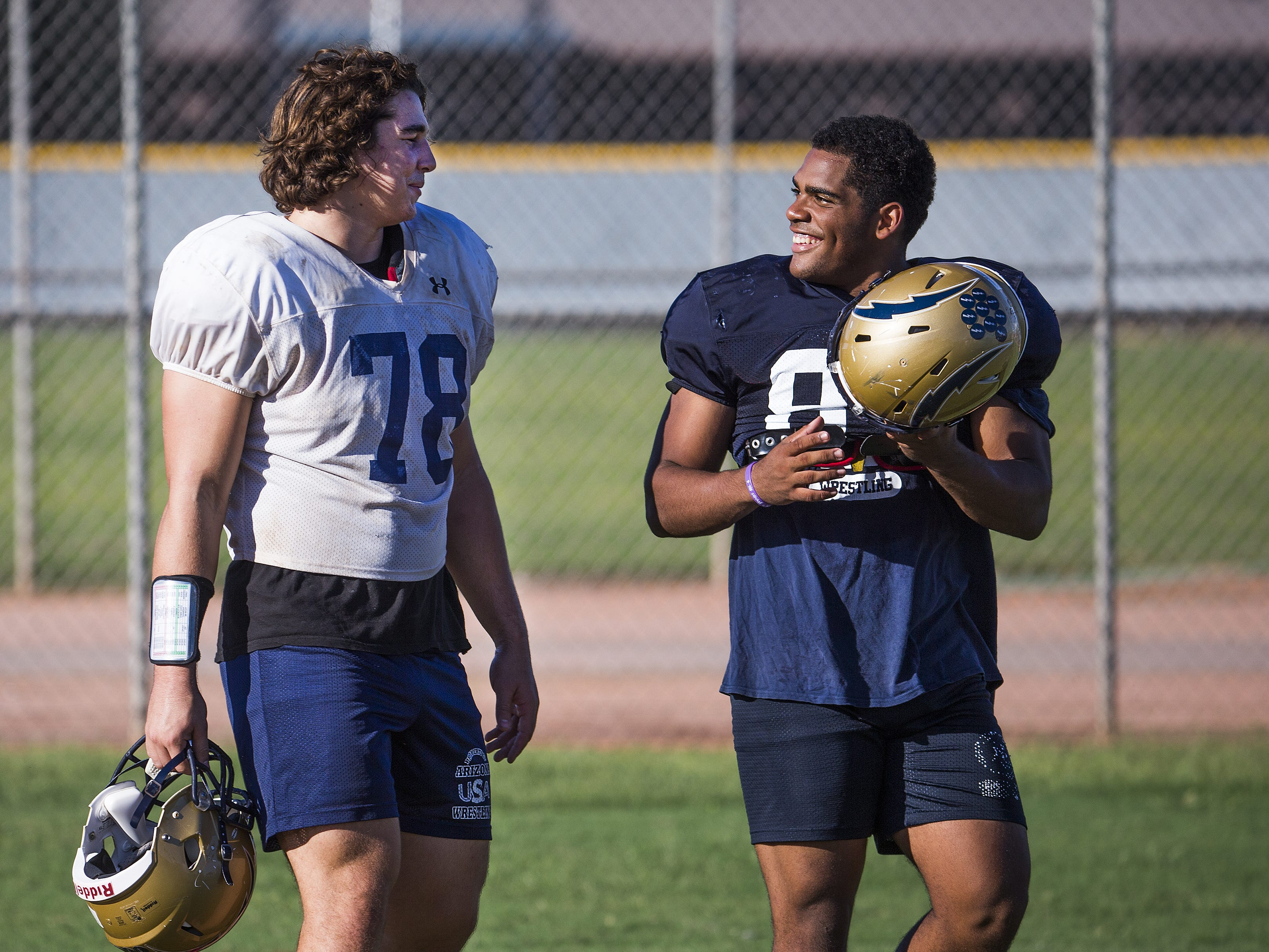 Desert Vista High School defensive linemen Brett Johnson, left, and Sebasthian Mingot talk during practice at the school, Wednesday, October 3, 2018.
