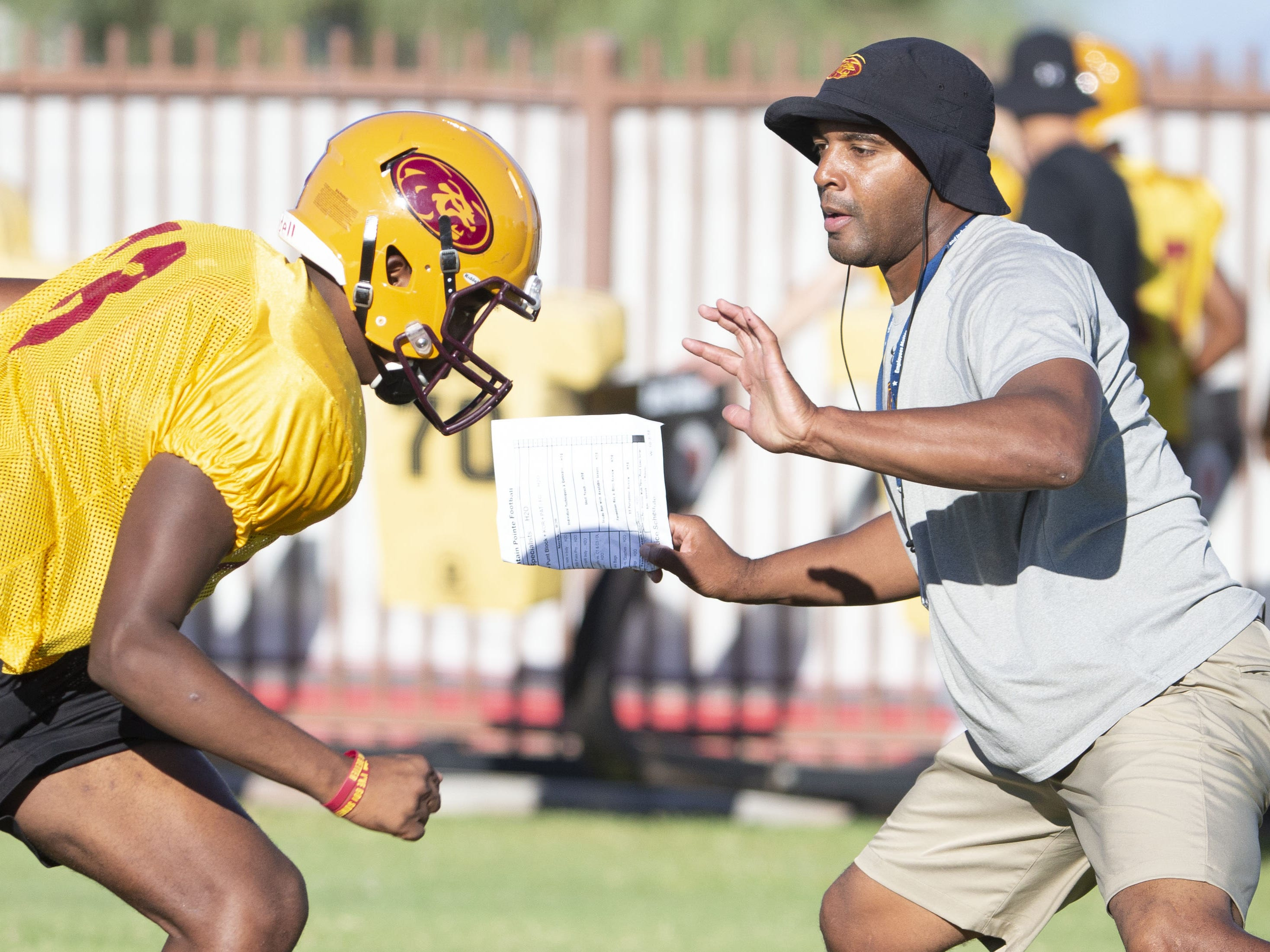 Mountain Pointe's defensive coordinator Conrad Hamilton leads by demonstration during practice in Phoenix on October 3, 2018.