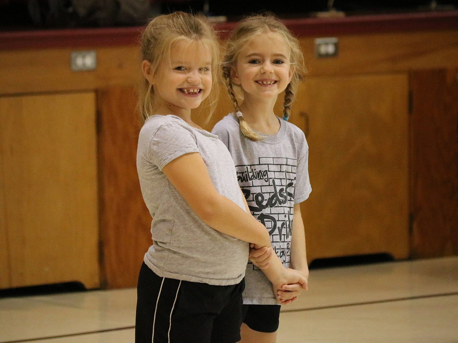 Micaela Wiechman and Suzanna Osborne, second graders at Immaculate Conception School, prepare to promenade during a square dance lesson on Wednesday.