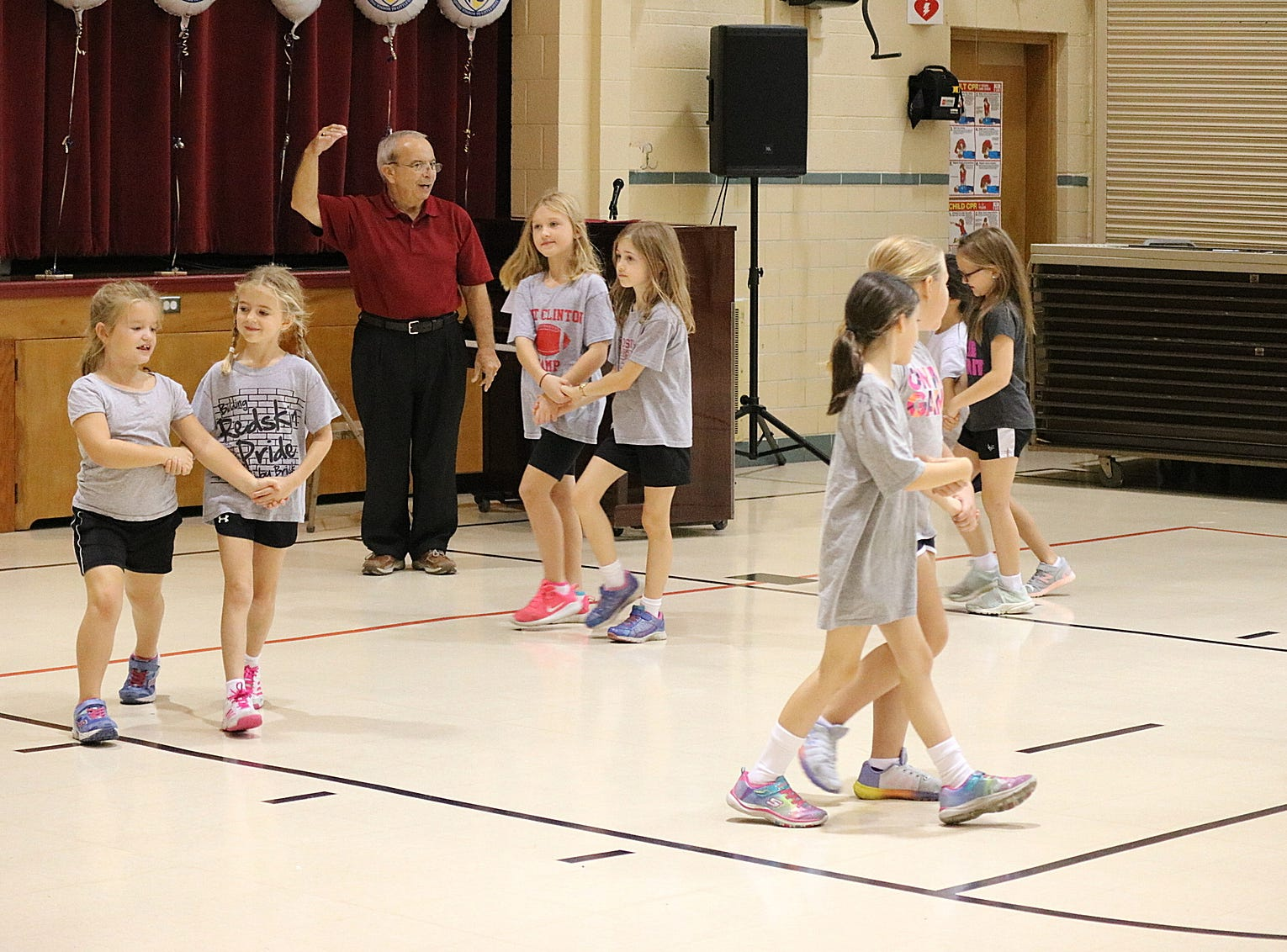 Second grade students at Immaculate Conception School practice the promenade with Greg Fox in preparation for the Boots and Buckles Pig Roast and Square Dance  on Oct. 20.