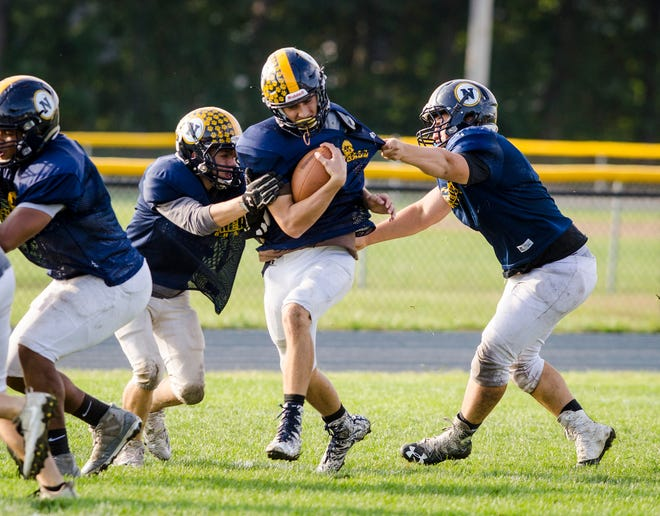 Port Huron Northern offensive linebacker Owen Schumacher, center, is grabbed by players as he runs the ball during a practice drill Wednesday, Oct. 3, 2018 at Port Huron Northern High School.