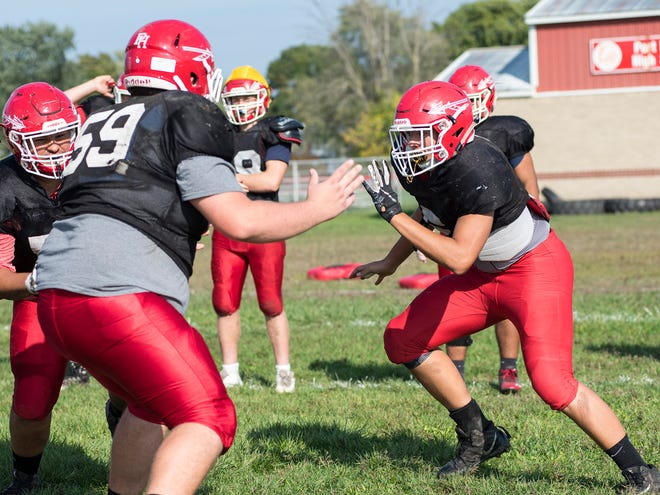 Port Huron High School defensive end Noah Kindle, right, runs around defensive lineman Mathew Phillips during practice Wednesday, Oct. 3, 2018 at the high school.