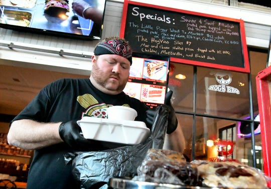 3 Hogs BBQ co-owner Matt Albright fills an order at the newly opened Central Market location in York Thursday, Oct. 4, 2018. There are also stores in Hanover and Spring Grove. Bill Kalina photo