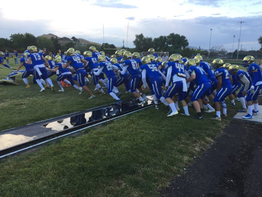 The Reed football team takes the field before a game last season.
