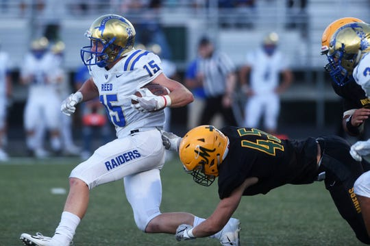 Reed's Trevor Kibala runs past a Bishop Manogue defender during their football game in Reno on Aug. 24, 2018.