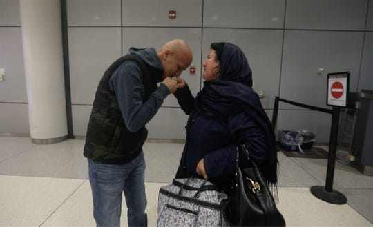 Burhanuddin (Burhan) Shamsuddin kissess his mother's hand as she, Madina Bikzad, weeps upon seeing him after five years.   She just arrived, Tuesday, Oct. 2 from Afghanistan via several flights.  Shamsuddin's medical team at University of Rochester Medical Center were able to bring her after about a year of trying.