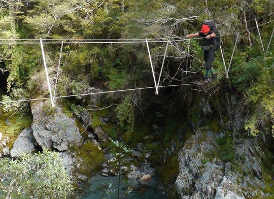 J. R. Harris crosses a three-wire bridge in New Zealand.