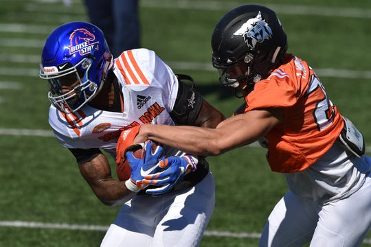 North Squad wide receiver Cedrick Wilson of Boise State (left) tries to pull away from cornerback Taron Johnson of Weber State (26) during Senior Bowl practice.