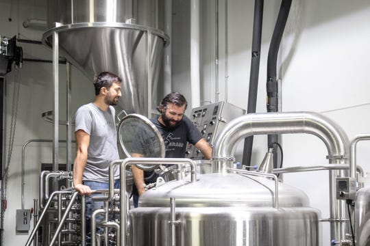 Blake Thompson of Fernson Brewing Co. and Steve Hartman of WoodGrain Brewing Co. work together on a new batch of beer.