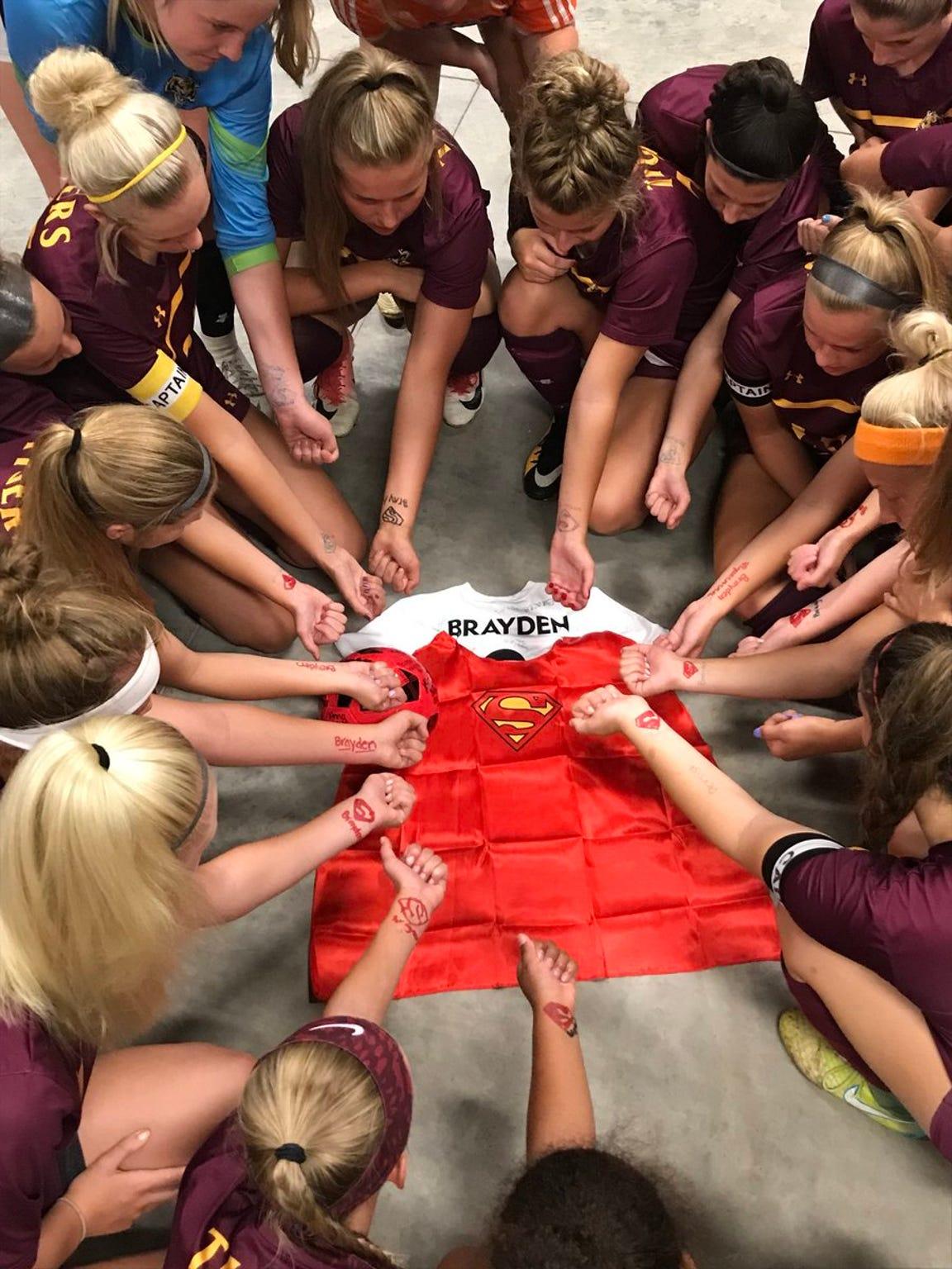 Members of the Harrisburg girls soccer team honor Brayden before their game against O'Gorman.