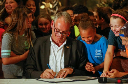 U.S. Secretary of the Interior Ryan Zinke and students from the WOLF School laugh as he dates a proclamation he signed during the 11th Annual Private Lands Partners Day at the White River Conference Center on Thursday, Oct. 4, 2018.