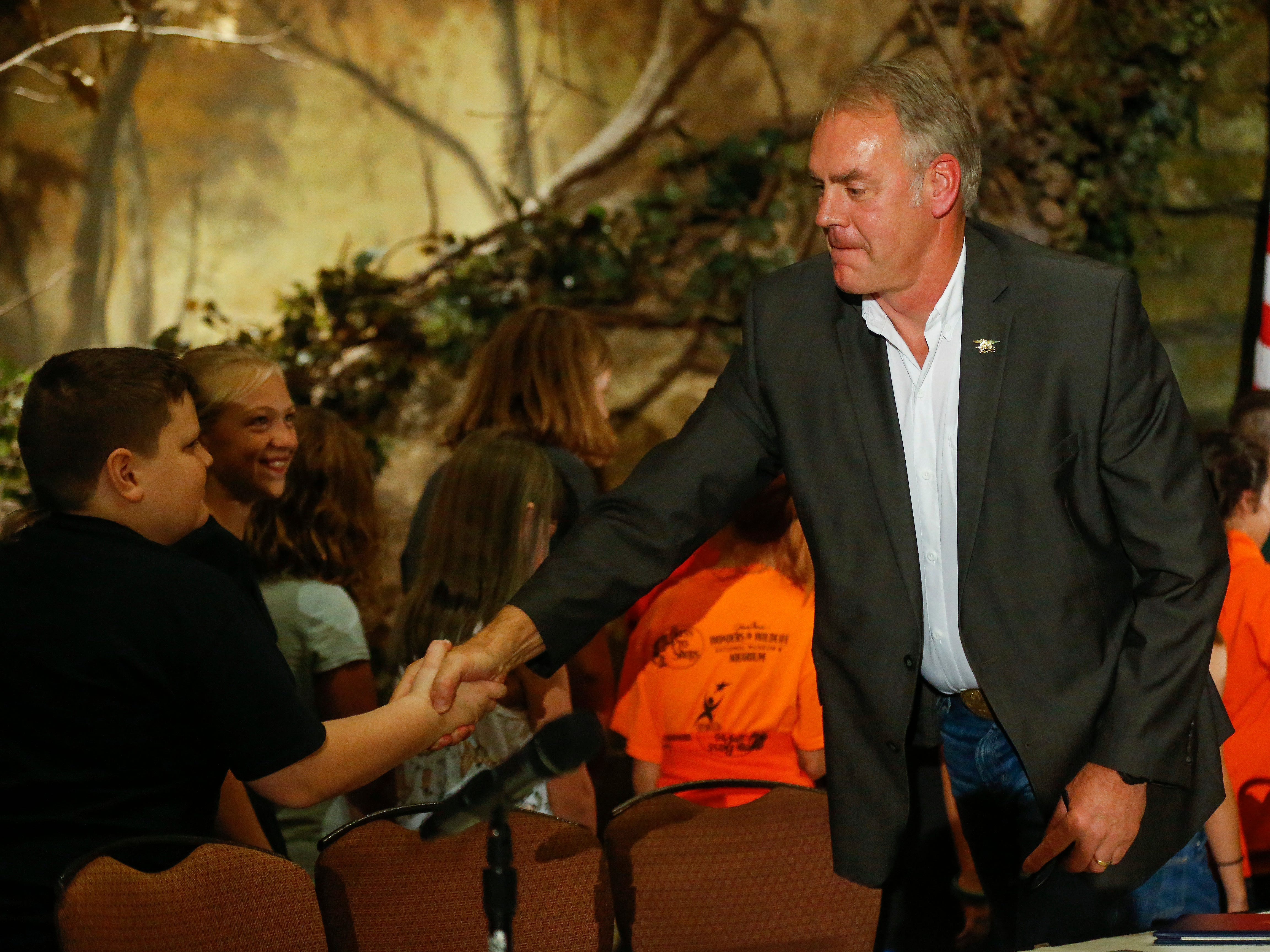 U.S. Secretary of the Interior Ryan Zinke shakes hands with students from the WOLF School after signing a proclamation during the 11th Annual Private Lands Partners Day at the White River Conference Center on Thursday, Oct. 4, 2018.