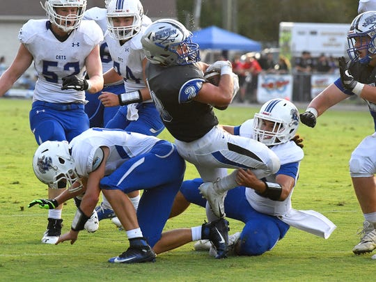 Robert E. Lee's Garrett Lawler spins with the football to break a tackle as he passes through two Rockbridge County players during a football game played in Staunton on Friday. August 31, 2018.