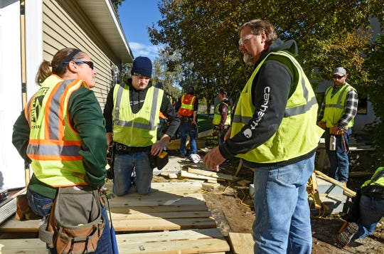 """Students in the St. Cloud Technical & Community College carpentry program install decks on a """"tiny house"""" Thursday, Oct. 4, at St. John's Episcopal Church in St. Cloud."""