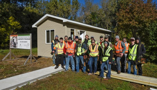 """Students in the St. Cloud Technical & Community College carpentry pose for a photograph while working on installing decks on a new """"tiny house"""" Thursday, Oct. 4, at St. John's Episcopal Church in St. Cloud."""