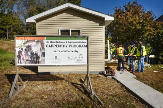 """St. Cloud Technical & Community College carpentry program students work on installing decks on a new """"tiny house"""" Thursday, Oct. 4, at St. John's Episcopal Church in St. Cloud."""